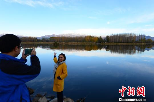 """10月28日,北京寒意袭人。2022年北京冬奥会三大赛区之一――延庆降雪,出现""""海坨戴雪""""壮丽景观,吸引了不少民众拍照。 于荣龙 摄"""