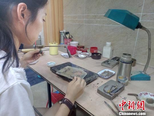 23岁的杨丽正在焊接银花丝制品。 王鹏 摄