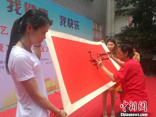 双管书画家曹平芳1日在儿童节广州活动现场展示双管书法 唐贵江 摄