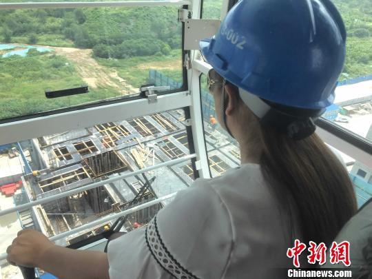 今年37岁的塔吊女司机潘雪华正稳坐在约50米高空的驾驶室中控制起重臂用吊钩移动重物。 杨飞 摄