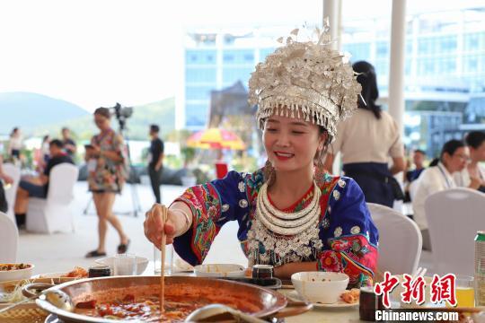 图为当地穿着少数民族服装的民众在品尝火锅。 瞿宏伦 摄