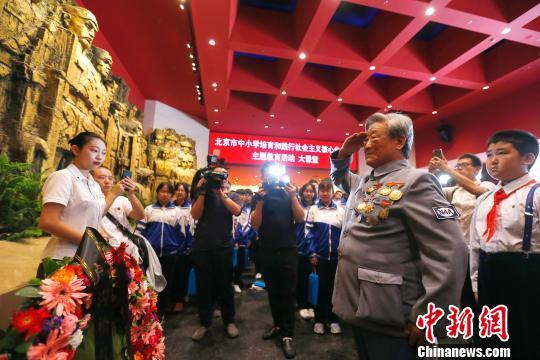 9月18日,新四军老战士焦润坤在中国人民抗日战争馆,带领少先队员代表向抗战英烈敬献花环,并给学生们讲述他和战友们抗战的故事。 富田 摄
