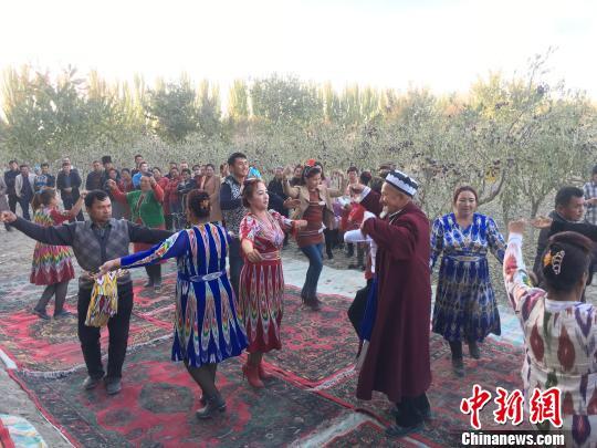 麦盖提县民众在丰收的枣园里跳起刀郎舞。 勉征 摄