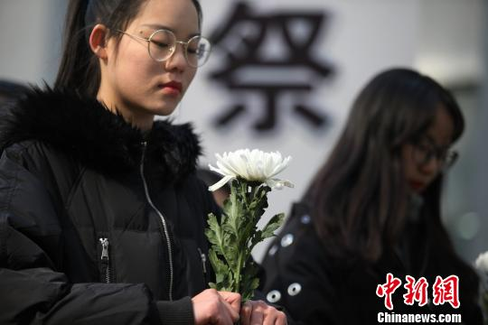 图为大学生持白色菊花悼念南京大屠杀遇难同胞。 孟德龙 摄