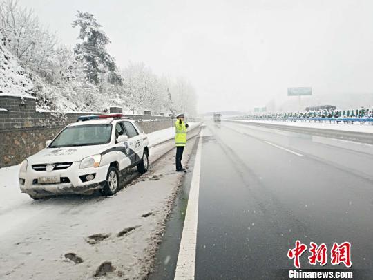 图为交警值守路边,随时监控突发状况。 刘瑞 摄