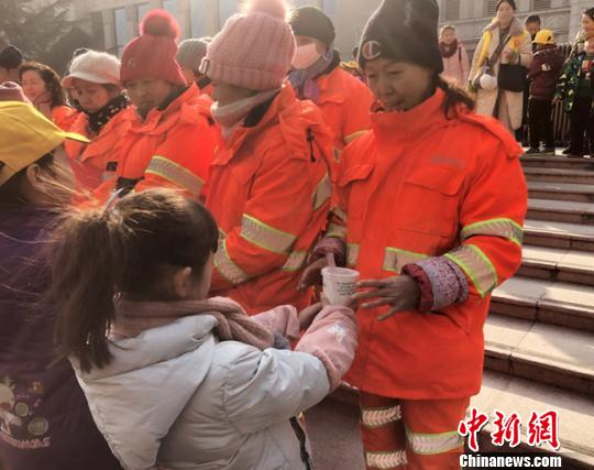 图为小志愿者为环卫工人送去腊八粥。姜尧 摄