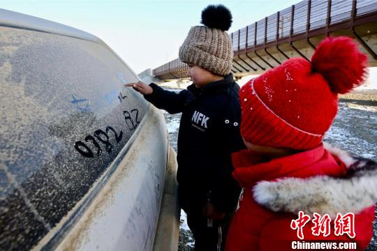 """托乎塔尔汗去巡线了,儿子在爸爸车的后窗上教妹妹写""""爸爸""""。 李国贤 摄"""