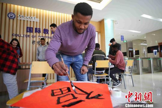 """中国石油大学(华东校区)海外留学生在写""""福""""字。 胡耀杰 摄"""