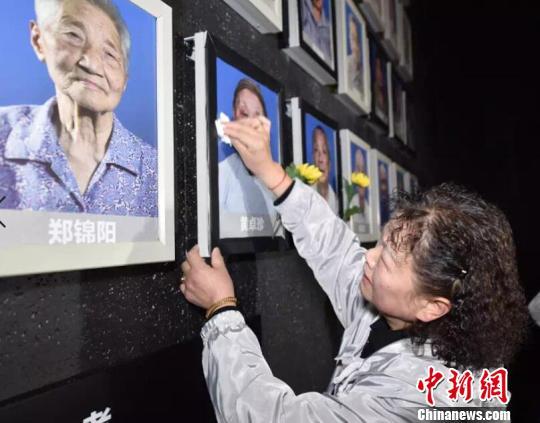 遗属在为老人擦拭照片、献上鲜花。 刘俊义 摄