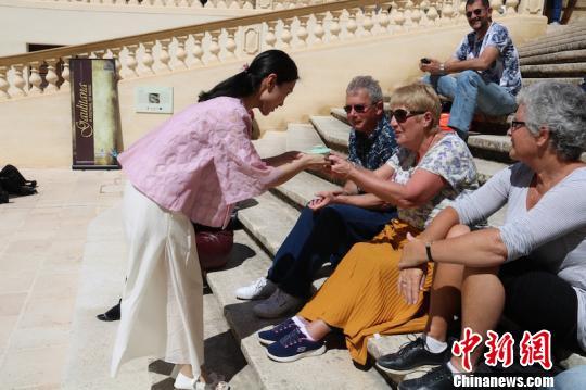 茶艺表演者向现场的外国友人奉上一口浓郁芬芳的香茶。遂昌提供