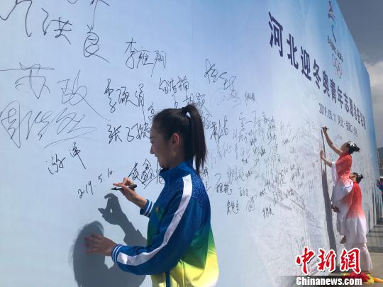 图为河北迎冬奥青年志愿者、张家口机械工业学校教师游洋在启动仪式现场主题背景墙上签名。 宋敏涛 摄