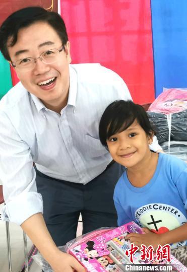 中国驻菲使馆谢永辉参赞为菲律宾孩子发放文具等礼物。 关向东 摄