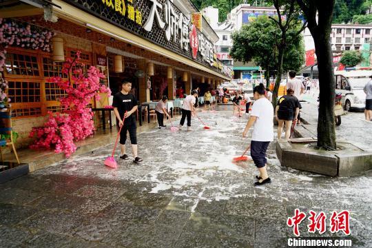 7月14日,桂林阳朔西街内涝消退,沿街商铺忙清淤。 唐梦宪 摄