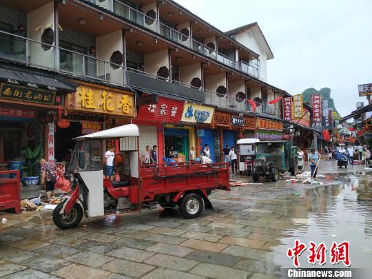 7月14日,桂林阳朔西街内涝消退,沿街商铺忙清淤。 欧惠兰 摄