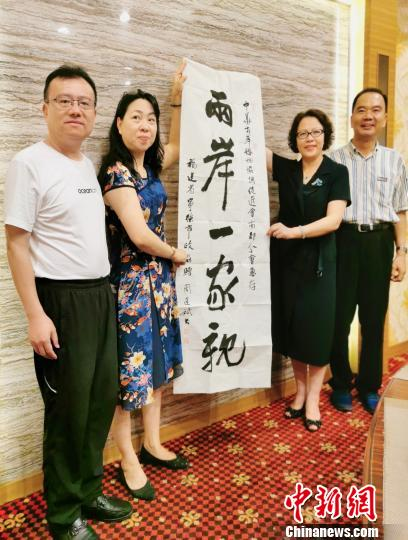 图为访问团成员现场书法,赠予中华两岸婚姻协调促进会。 吕巧琴 摄