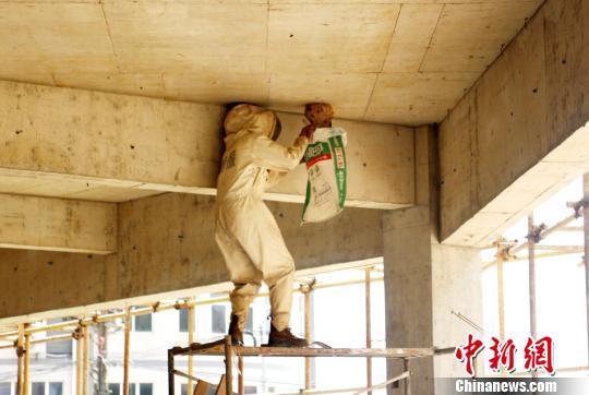 救火员用编织袋套住蚂蜂瓮碌施戴除。孝感消防供图