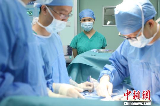 志愿者在体验手术室工作 梁建钟 摄