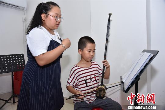 11岁的王若城练习北管多年,已经掌握了唱腔和弦乐演奏。 陈龙山 摄