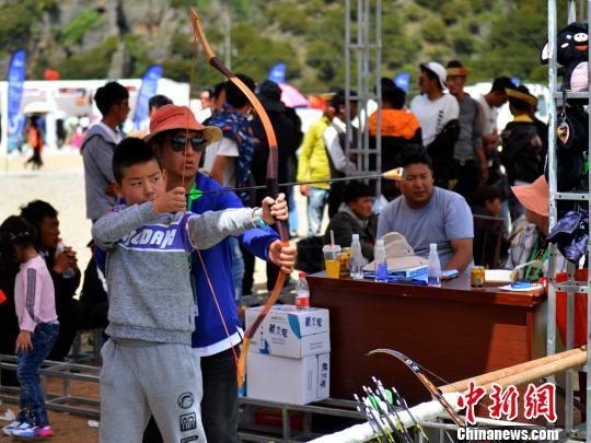 """8月16日,在巴松措景区举办的活动上,游客体验当地有名的""""工布响箭"""",该箭在发射后会发出啸声。 江飞波 摄"""