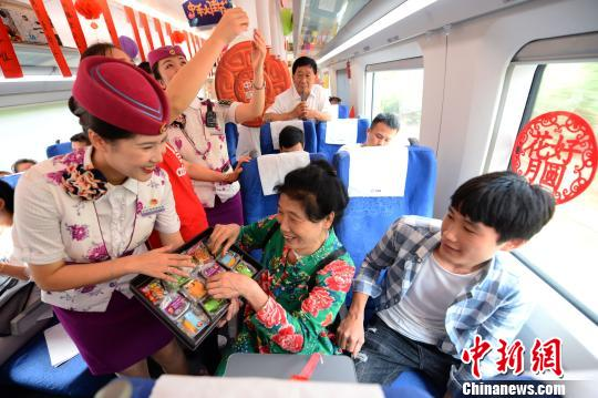 图为G2308次列车乘务员正在给游客收放月饼。 沈背齐 摄