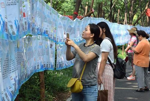 """资料图:一名市民在济南千佛山公园举行的""""七月七相亲大会""""上用手机记录相亲信息。记者 徐速绘 摄"""
