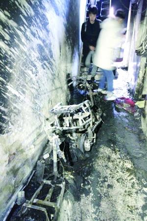 ▲位于楼梯口的两台电动车已被烧得只剩下骨架。图片来源:北京晨报