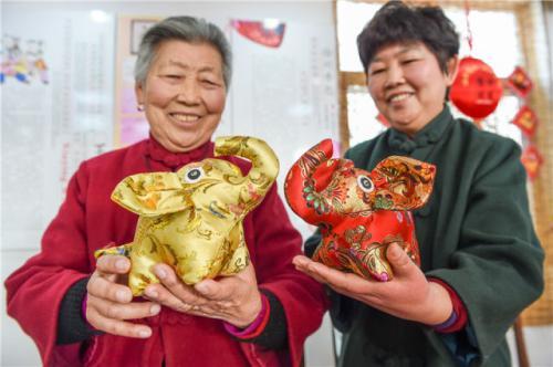 徐州市贾汪区马庄村村民王秀英老人(左)展示香包工艺品(12月13日摄)。新华社记者李博摄