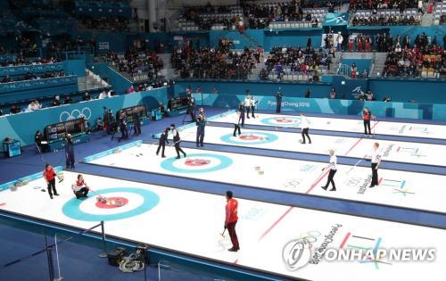 距离2018平昌冬奥会开幕仅剩一天的8日上午,在江原道江陵冰壶中心,冰壶混合项目预赛第一轮比赛进行中。这是平昌冬奥会第一场比赛。(图片来源:韩联社)