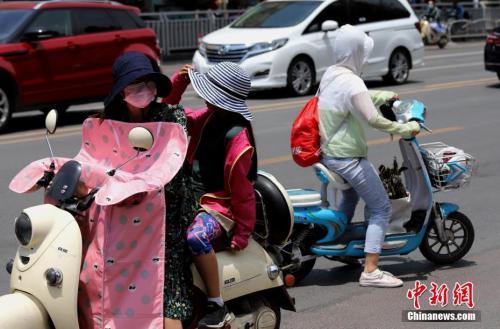 """资料图:6月6日,河南郑州遭遇高温天气,出行民众""""全副武装""""遮阳防晒。<a target='_blank' href='http://www.chinanews.com/'>中新社</a>记者 王中举 摄"""