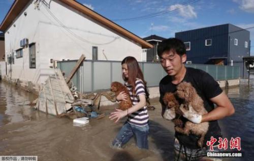 当地时间7月8日,日本仓敷,当地民众将宠物带离被洪水围困区域。