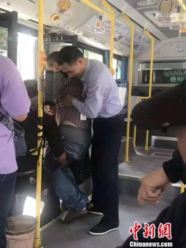 图为:公交车司机抱起腿脚不便的乘客下车 浙江省临海市委宣传部供图 摄