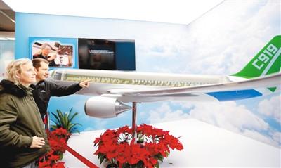 """图为在中国国家博物馆举行的""""伟大的变革——庆祝改革开放40周年大型展览""""现场,外国观众在中国国产大飞机C919展台前参观。 新华社记者 潘 旭摄"""