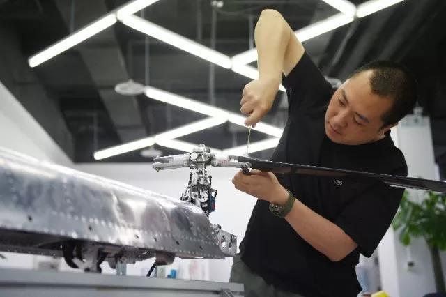 """△2017年5月4日,""""动批""""天皓成服装批发市场改建成的""""宝蓝金融创新中心""""内,一位员工调试无人机。"""