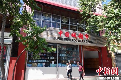 """当地时间3月24日,行人从多米尼加首都圣多明各""""唐人街""""的华人超市前走过。这里分布着数百家华人店铺、商场和中餐馆,是旅居多米尼加华侨华人的主要聚集地。 莫成雄 摄"""