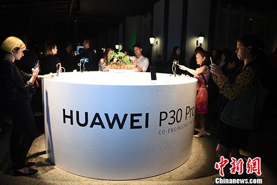 图为与会嘉宾现场体验华为P30系列高端手机。 中新社记者 莫成雄 摄
