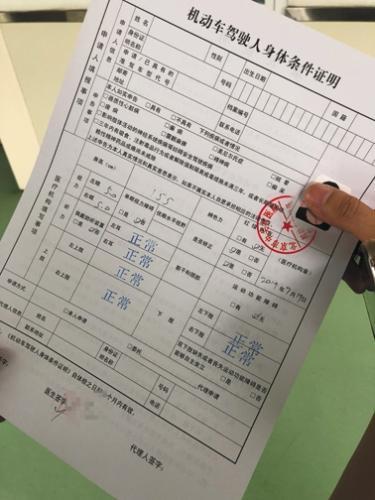 昨日,中关村医院体检中心,一位驾驶员拿到已盖章的《机动车驾驶人身体条件证明》,上面多处空白,自行填写。新京报记者 张静姝 摄