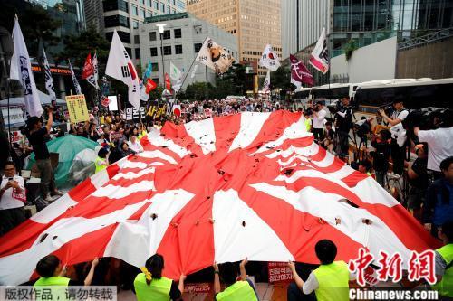 材料图:韩百姓寡撕扯着朝阳旗,正在日本驻韩使馆前抗议。