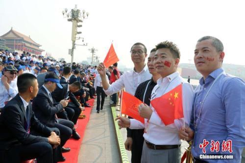 资料图:10月1日,庆祝中华人民共和国成立70周年大会在北京隆重举行。约2000名海外华侨华人在现场见证了历史时刻。他们表示,国庆庆典展现了中华民族的自信和威严,凝聚起了全球侨胞的心。图为来自巴布亚新几内亚的薛辉雄等在观礼台合影。中新社记者 任海霞 摄