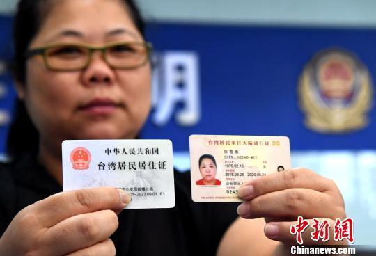 资料图:台胞陈筱薇展示自己领到的台湾居民居住证和其台湾居民来往大陆通行证。 张斌 摄