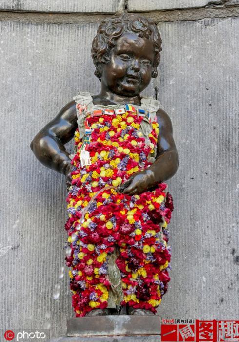 """当地时间2019年8月12日,比利时布鲁塞尔,比利时艺术家Geoffroy Mottart在给比利时地标""""撒尿小童""""布置鲜花装饰。"""