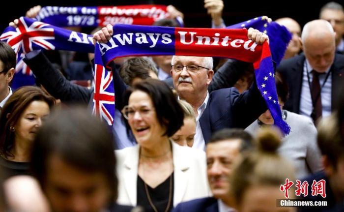 """图六:当地时间1月29日,欧洲议会批准""""脱欧""""协议。图为投票结束后,在场议员高举""""永远团结""""旗帜。<a target='_blank' href='http://www.chinanews.com/'>中新社</a>发 欧盟供图"""