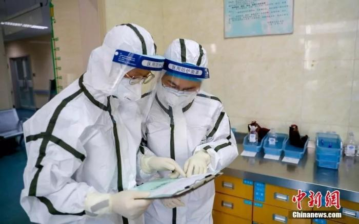 2月3日,医院隔离病房内,两名医务人员核对患者治疗单。中新社记者 张畅 摄