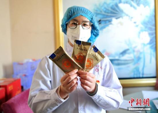 资料图:医护人员展示根据《新型冠状病毒感染的肺炎诊疗方案》研制的中药制剂。中新社记者 韩冰 摄