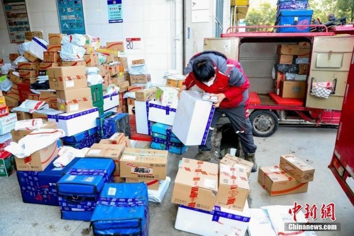 2月9日,武汉汉口将军路一家快递公司的快递点,快递员们整理到站的快件。新冠肺炎疫情之下,大批民众选择线上购物,快递员比往常更忙碌。中新社记者 张畅 摄