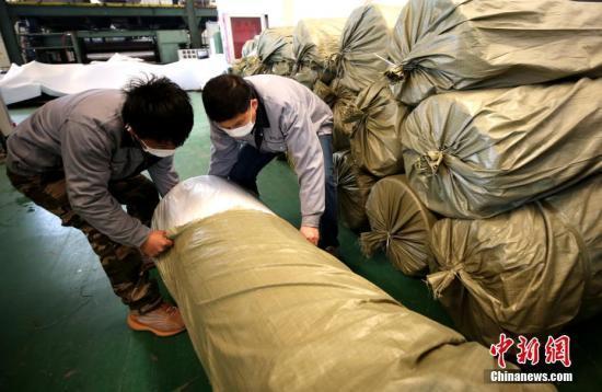 2月19日,位于河北省大廠回族自治縣高新技術產業開發區的金億綸新材料科技(廊坊)有限公司的工作人員在為生產的熔噴非織造布打包。 中新社記者 宋敏濤 攝