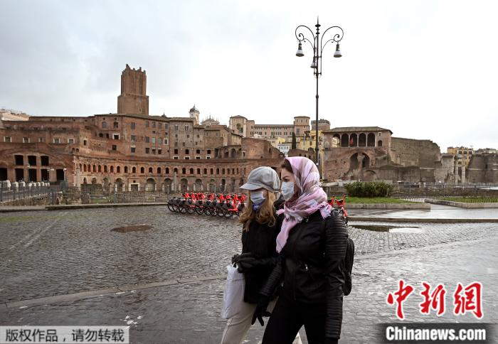 当地时间2020年3月3日,两名戴着口罩的女子从意大利罗马图拉真论坛遗址前走过。