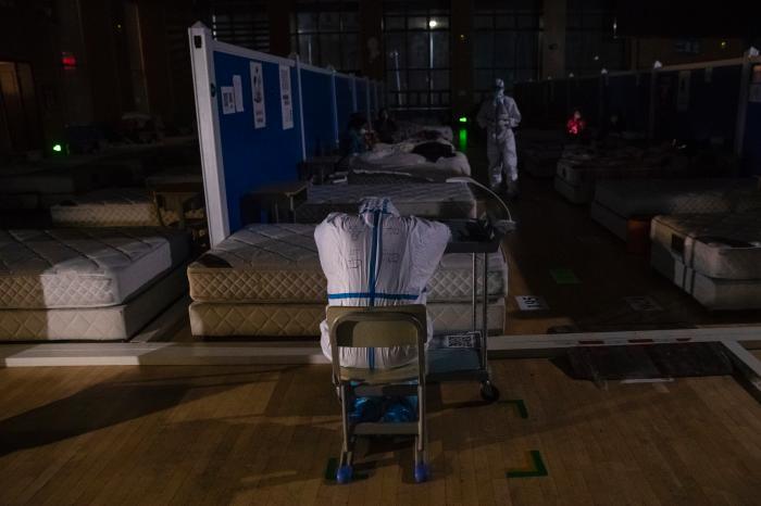 3月9日晚,在位于武汉市洪山体育馆的武昌方舱医院,一名医务人员趴在小架子上休息。