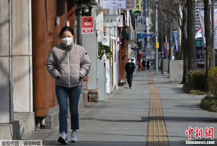 2月27日,一名女子戴着口罩走在韩国大邱街道上。