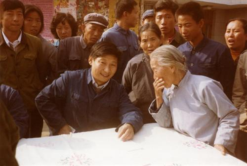 1983年,时任河北正定县委书记的习近平(前排居中),临时在大街上摆桌子听取老百姓意见。 图片来源:新华社