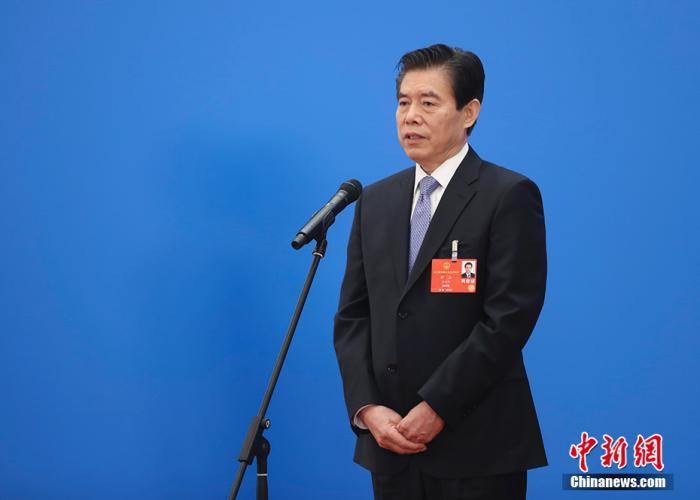 """5月25日,第十三届全国人民代表大会第三次会议在北京人民大会堂举行第二场""""部长通道""""采访活动。图为商务部部长钟山通过网络视频方式接受采访。 中新社记者 杜洋 摄"""